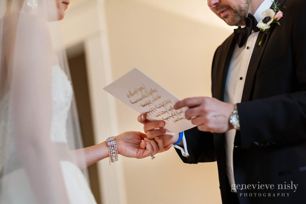 The bride holds the groom's hand as he reads the letter she wrote for him.