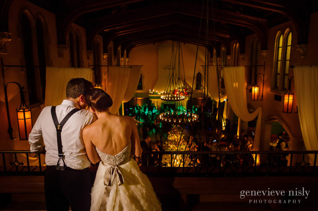 Bride and groom look over their reception from the balcony.