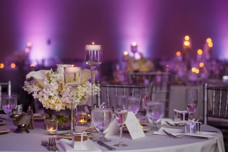 A close up photo of a table at the Hilton Garden Inn Cleveland East set for a reception with silver chairs and round tables set with white linens and white floral centerpieces and candles in tall glass stands and purple uprights on the back walls which are out of focus.