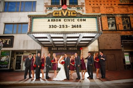 A bride and groom standing with their wedding party in red dresses and black tuxedos on the street outside the Akron Civic Theater box office window in Akron, Ohio.