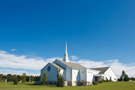 A beautiful image of the outside of the white Mayfield Church with it's white steeple set on a green grassy hill under a sunny blue sky with white puffy clouds.
