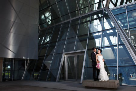 A bride in her white gown leaning back against a groom in his black tuxedo up against the grey and blue tinted glass windows of the Akron Art Museum in Ohio.