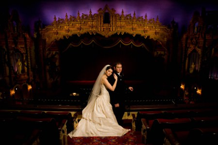 A bride and groom standing in the darkened Akron Civic Theater in the main aisle with the stage behind them with purple and gold uprights.