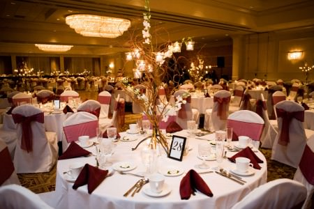An image of a wedding reception set up at the Akron Fairlawn Hilton with white and maroon linens and golden lighting.