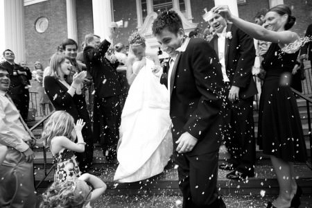 A black and white image of a bride and groom holding hands, smiling and ducking while exiting the Akron Reformed Church as the wedding guests toss bird seed at them.