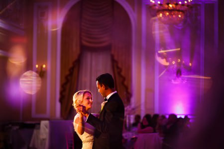 A picture of the upper half of a bride and groom in focus slow dancing in the middle of the picture while the rest of the photo is out of focus and glowing in a purplish pink color from the lighting in the ballroom during a wedding reception while guests are seated watching from the left side of the photo.