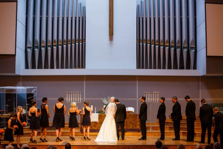 A bride and groom standing with their heads together facing the pastor with the wedding party all in black attire at the modernly decorated Bay Presbyterian Church with wooden stage and steps and a grey wall with huge metal grey organ pipes in the background.