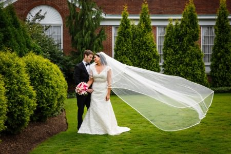 An image of a bride in her short sleeve lacy white gown standing side by side the groom in his black tux looking into each other's eyes while standing on the grassy lawn on a sunny day with the brides veil blowing in the wind with the red brick Beechmont Country Club and tall green shrubs in the background.