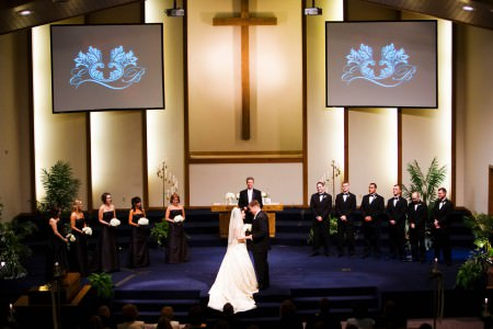 A bride and groom stand on the blue carpeted altar inside the Bethel Temple holding hands and looking into each other's eyes under a large wooden cross while the while the wedding party and clergy look on.