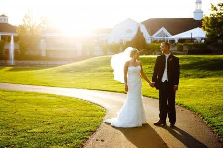 An image of a bride and groom standing in the right side of the photo holding hands and looking at each other on a curved cement sidewalk with a green rolling lawn behind them and the white Blair Center building in the background with a warm golden sunset starting behind the building and casting a glow over the photo.