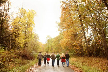 An image of a family of seven walking away from the camera down a dirt road at the bottom of the photo in the fall all wearing fall colors under a cloud covered sky with tall trees with brown trunks and green, yellow, and faded orange leaves lining the road at Brandywine Falls in Ohio.