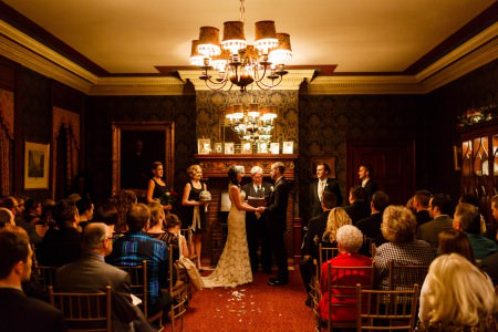 A bride and groom stand facing each other holding hands during their wedding ceremony inside a room with a fireplace at the Canton Club that had reddish-orange carpet, ornate wallpaper, and chandeliers, while the guests sit in golden backed chairs and the two bridesmaids and two groomsmen look on,