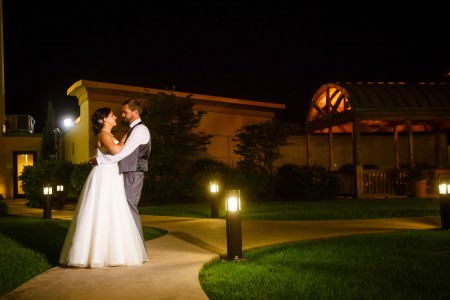 A bride and a groom stand outside and night holding each other on a cement sidewalk lined with golden lights on waist high pillars the the Canton Courtyard Marriott in the background.