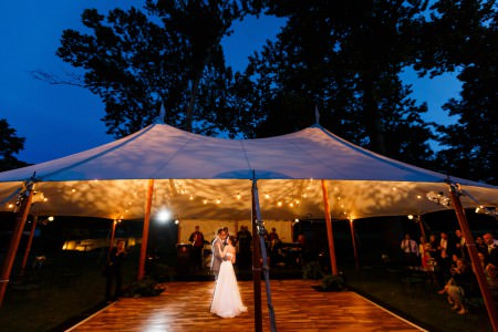 An image of a bride and groom slow dancing on a wooden pallet floor under a white tent strung with cafe lights that is in the center to the lower half of the photo and the upper half shows a bold blue dusk sky with dark trees silhouetted.