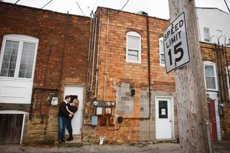 An engaged couple both wearing black sweaters with jeans stand in each other's arms facing each other against a white door set in a red brick building with silver pipes and meters attached to the building on a side street with a white speed limit 15 sign in the foreground.