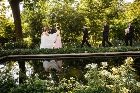 A bride leading the jewish wedding party on path in front of a reflecting pool at the Cleveland Botanical Gardens where the groom is standing immediately behind her and a bridesmaid is close by holding the back of her wedding gown from trailing on the ground.