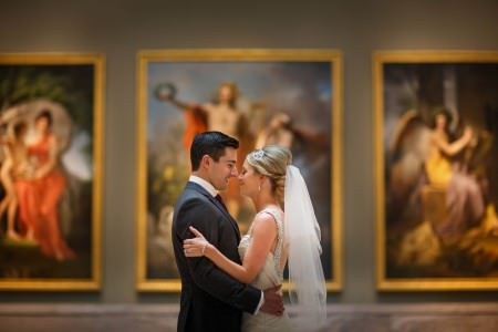 A bride and groom nose-to-nose smiling and holding each other inside a gallery at the Cleveland Museum of Art while three gold framed paintings are out of focus in the background.