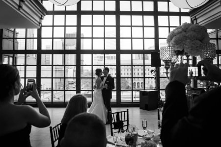 A black and white picture of a bride and groom slow dancing in front of a wall of windows at the Club at Key Center overlooking downtown Cleveland and the city skyline while the guests at the reception watch and take pictures.