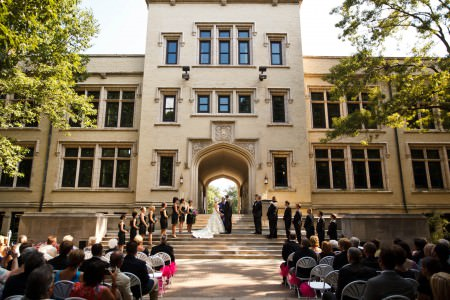 An image of a wedding ceremony taking place outdoors on the cement steps of a cream colored building on the grounds of the College of Wooster where the bride and groom are the central focus and the wedding party is lined up in a v shape while the wedding guests sit and watch under a sunny sky.