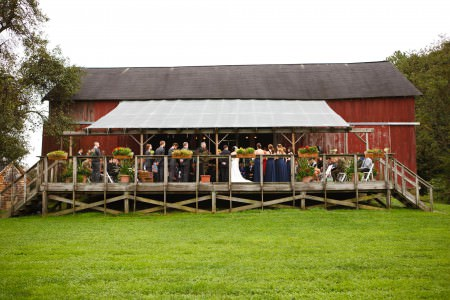 An image of an outdoor wedding ceremony taking place on a wooden deck in front of a red barn at the Conrad Botzum Farmstead in the Cuyahoga Valley National Park in Ohio.
