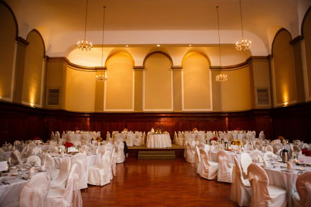 A wide angled picture taken of The Corinthian set up and decorated for a wedding reception with round tables and chairs covered in white linen with bows on the wooden floor in the lower half of the photo and the golden colored back wall with arched cut outs and candelabras hanging from the ceiling in the upper half of the photo.