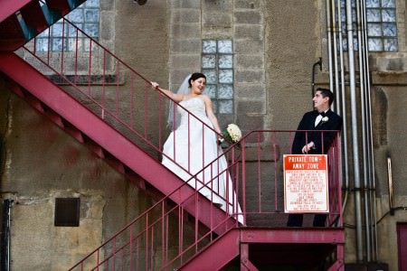 A photo of a bride and groom standing on red metal steps inside a very industrial looking cement building where the groom is standing on the landing of the steps in center right of the photo in his black tuxedo leaning against the stone wall and the bride is wearing a white strapless dress and veil holding a white rose bouquet while standing up a few steps looking back over her shoulder and smiling at the groom in Cuyahoga Falls.