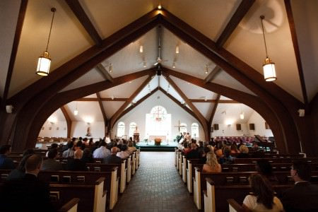 A picture of the inside of the Devine Word church from the back of the center aisle looking down toward the alter past the white and dark wooden pews full of wedding guests under a triangular ceiling with large wooden beams.