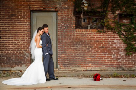 An image of a bride in her white gown hugging the groom from behind in front of a grey door on a brick building with her bright red bouquet laying on the sidewalk in downtown Akron.
