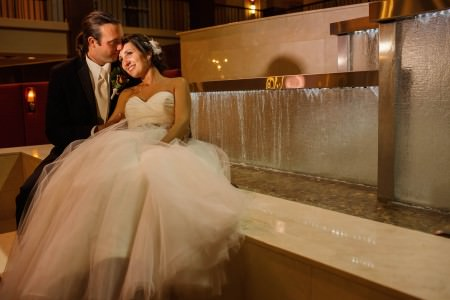 A bride and groom sitting on the marbled edge of the multi-level waterfall of the lobby of the Embassy Suites in Cleveland, Ohio where the bride is leaning back into the grooms arms and he is kissing her forehead.
