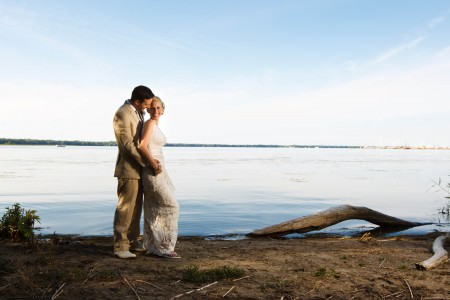 An image of a bride in a white lacy sleeveless wedding gown and white flip flops is leaning back into the arms of her groom in a tan suit standing in the middle left of the photo on the sandy shorelines of Lake Erie with a large piece of tan driftwood to the right of the couple and the lake as the background.