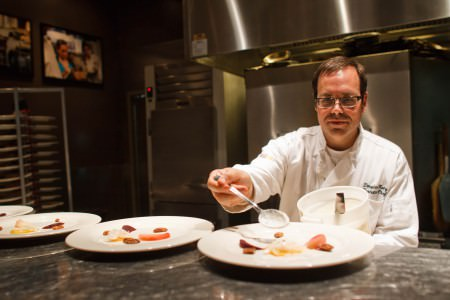 A photo of the executive chef wearing white plating appetizers on white plates sitting on dark granite counter tops taken inside the kitchen of Fire Food and Drink.