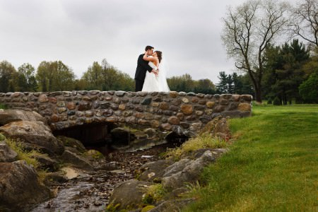 A bride in her white gown embracing her groom in a black tuxedo standing under grey skies on a cobblestone arched bridge at the Firestone Country Club in Ohio.