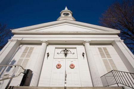 An image of the solid white First Congregational Church in Twinsburg looking up at a sharp angle directly from the cement steps straight up the front of the church towards the steeple under a brilliant deep blue sky with the double doors in the middle of the picture with a red and white floral wreath on each door.