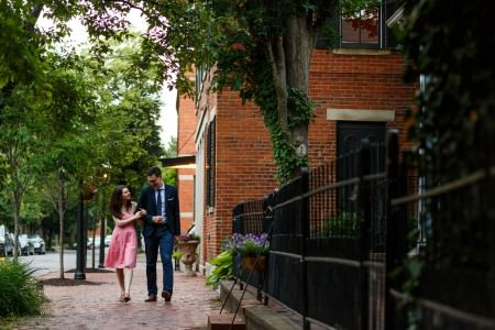 An engaged couple stroll arm and arm in the center left of the photo where the woman is wearing a short strapless pink dress and the man is wearing a blue suit coat over a button-down shirt and jeans on a brick sidewalk walking past a brick building on the right of the photo with a black wrought iron fence in the right side of the photo and green trees on either side in German Village near Columbus, Ohio.