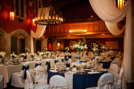 A reception hall decorated in navy blue and white linens with white hydrangeas and calla lilys at the stunning Glenmoor Country Club with red walls, stone archways, and white drapes hanging from the ceiling.