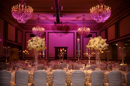 An image of the Gold Ballroom decorated for a reception with long rectangular tables draped in cream colored linens with flower puffs and draped chairs lining the tables as well as tall ornate white flower arrangements and tall brass candelabras with the walls of the room glowing in a purplish pink color from the lighting.
