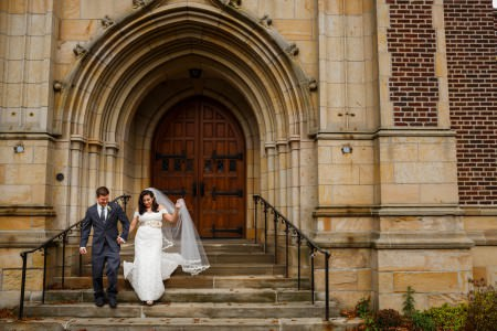 A bride and groom holding hands while walking down the stone steps exiting the Grace Lutheran Church with the ornate stone multi-arched doorway with wooden double doors.