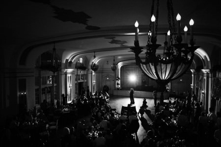 A black and white bird's eye view of a bride and groom slow dancing during the reception underneath ornate light fixtures at Greystone Hall in Akron, Ohio.