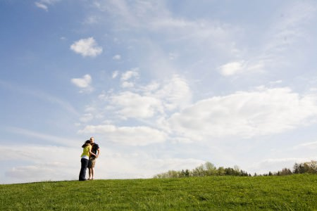 A woman in a yellow top with blue jeans embraces her fiancé in a golf shirt with tan shorts on the grassy knoll of the Hinkley Reservation in Ohio with trees and blue sky and puffy clouds in the background.