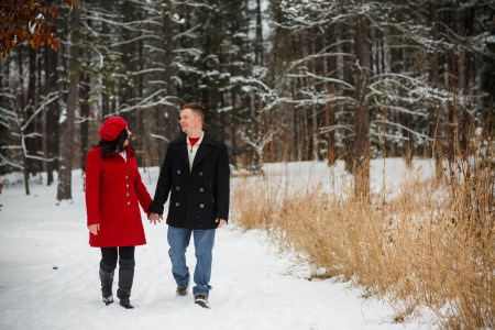 A picture of an engaged couple strolling hand in hand in the left of the photo in the snow at the Holden Arboretum where the man is wearing jeans and a black winter coat and the woman is wearing a bright red winter coat with a matching hat with tall trees with bare winter branches behind them covered with a dusting of snow and spindly tan weeds in the right of the photo.