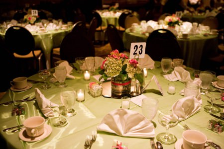 An image of a darkened reception room filled with round tables covered in light green satin table clothes with one table being the focus in the bottom half of the photo set with white napkins and white dishes along with green hydrangea and pink flower arrangement in the center of the table at a Holiday Inn.