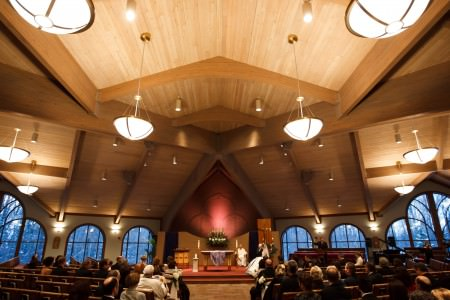 An image of a bride and groom sitting on the altar of the uniquely shaped Holy Angels Church in Ohio with a wooden planked ceiling, a wall of arched windows, and red carpeted altar area.
