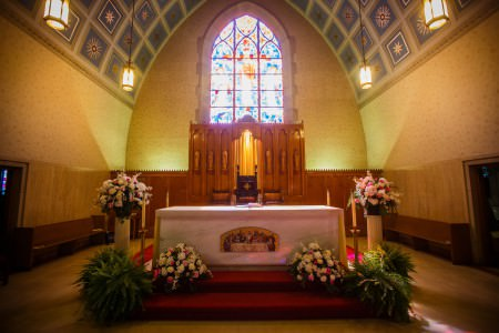 A photo of the arched domed sanctuary of the Holy Redeemer Church white a stained glass window in the background and square blue ceiling pattern with a rectangle table at the center of the photo lined with four white and pink flower arrangements and two ferns.