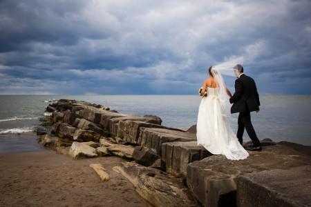 A wedding couple walk out onto a Lake Erie break stone wall holding hands while the bride's veil blows in the wind at Huntington Beach in Rocky River, Ohio under a dark and cloudy overcast sky.