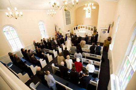 A photo taken from the right corner of the balcony overlooking the brightly lit sanctuary with blue and white pews and white walls while the bride is being escorted to the front of the altar and the guests and wedding party are standing inside the United Methodist Church in Independence, Ohio.