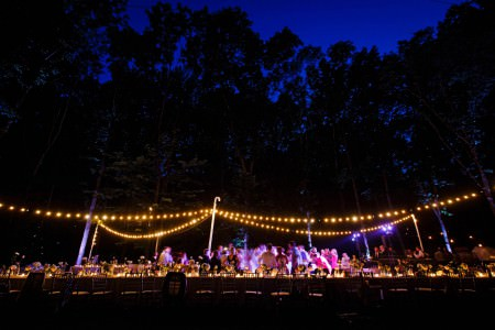 a stunning image taken at dusk of wedding guests dancing outdoors under a canopy of cafe lights and purple lights shining on the dance floor positioned just beyond the golden glowing long table with chairs and a deep blue sky as a backdrop at the Inn at Honey Run in Millersburg, Ohio.