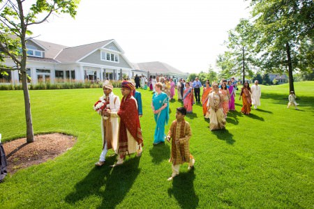 A photo taken outside on a bright sunny day of Indian wedding guests in their bright sarees following the groom across a bright green lawn with a grey and white building in the background at the Jefferson Country Club.