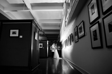 A black and white image of a bride in her white strapless wedding gown kissing her groom in his white jacketed tuxedo inside the Joseph Saxton Gallery of Photography with tiny pin spotlights shining on the black framed gallery photos.