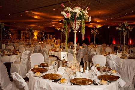 A photo taken of a room decorated and set for dinner during a wedding reception at La Malfa with round tables and chairs covered in white linen set with gold charger plates and floral arrangements sitting on tall cream wrought iron stands all under a ceiling draped in cloth decorated with twinkle lights.