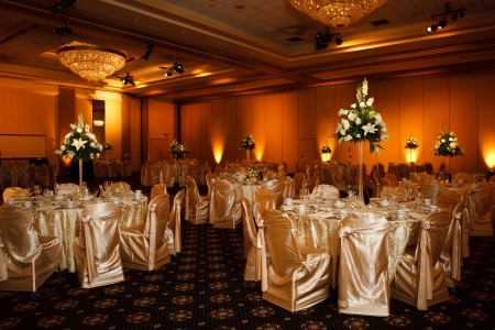A photo of a room decorated for a wedding reception with cream colored silk table cloths and chair covers as well as tall white floral arrangements set in the middle of the round tables and soft golden orange uprights set around the walls of the room at LaCentre.